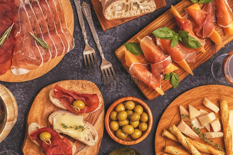 Italian food background with ham, cheese, olives. royalty free stock image