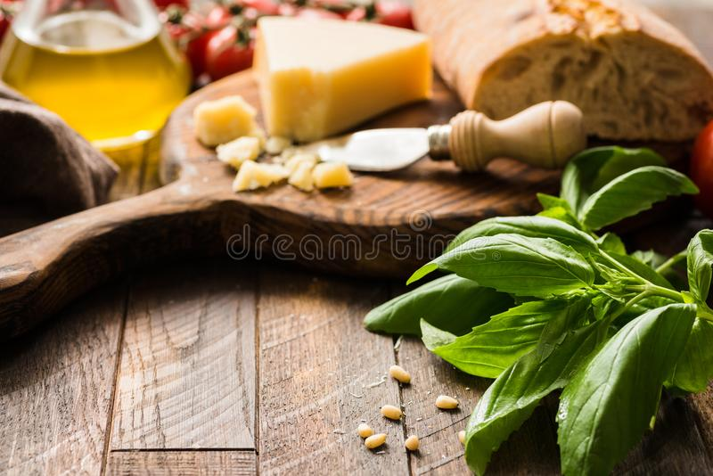 Italian food background with parmesan cheese, olive oil, ciabatta and basil leaves on rustic wood. Copy space for text, selective focus stock photography