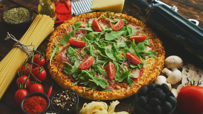 Italian food background with pizza, raw pasta and vegetables on wooden table royalty free stock image