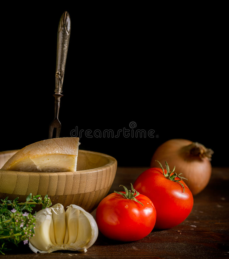 Italian food. Background with tomatoes, parmesan, garlic, and thyme on black background stock photography
