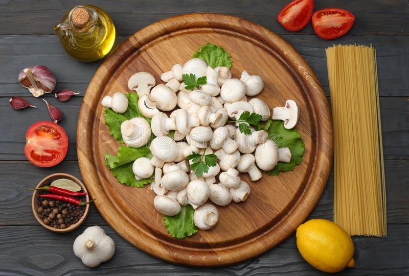 Italian food background, with tomatoes, parsley, spaghetti, mushrooms, oil, lemon, peppercorns on dark wooden table. Top view royalty free stock image