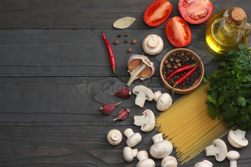Italian food background, with tomatoes, parsley, spaghetti, mushrooms, oil, lemon, peppercorns on dark wooden table. Top view stock images