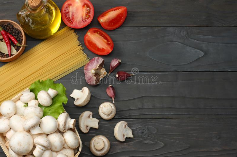 Italian food background, with tomatoes, parsley, spaghetti, mushrooms, oil, lemon, peppercorns on dark wooden table. Top view royalty free stock photography