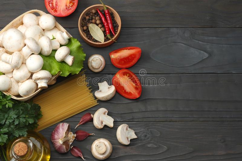 Italian food background, with tomatoes, parsley, spaghetti, mushrooms, oil, lemon, peppercorns on dark wooden table. Top view stock photography
