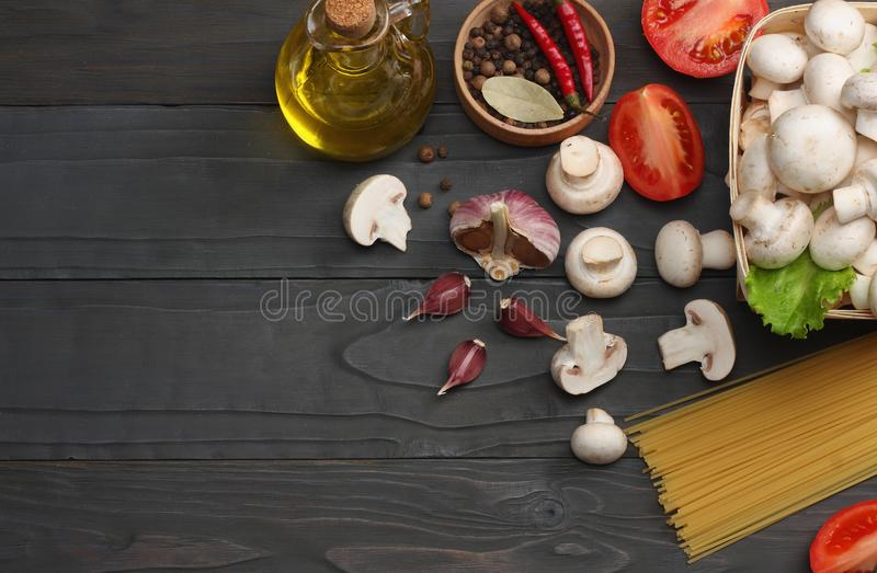 Italian food background, with tomatoes, parsley, spaghetti, mushrooms, oil, lemon, peppercorns on dark wooden table. Top view stock image