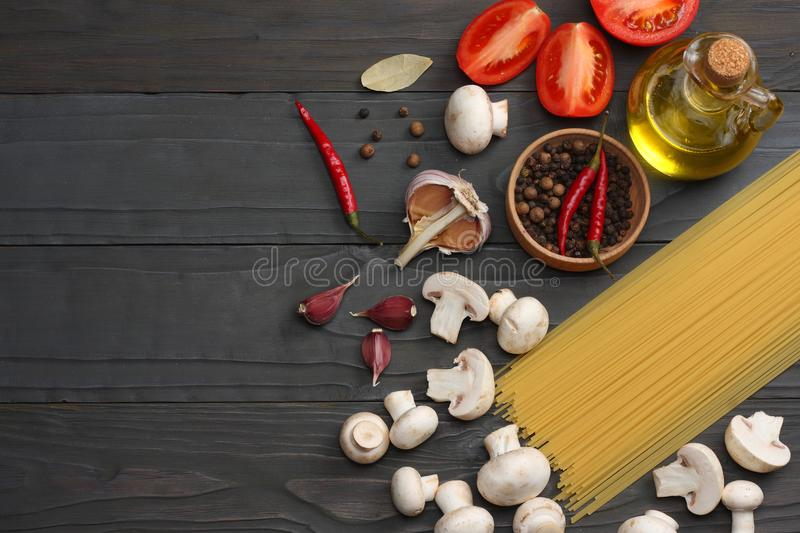 Italian food background, with tomatoes, parsley, spaghetti, mushrooms, oil, lemon, peppercorns on dark wooden table. Top view royalty free stock images