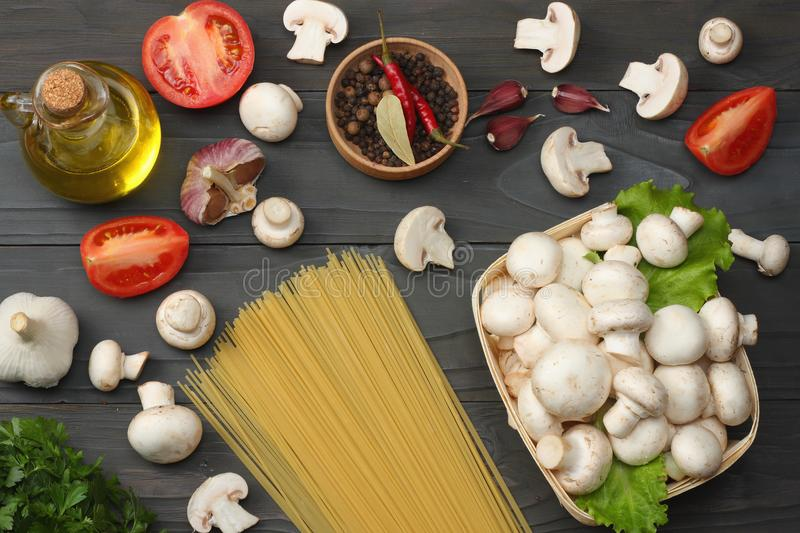 Italian food background, with tomatoes, parsley, spaghetti, mushrooms, oil, lemon, peppercorns on dark wooden table. Top view stock photo