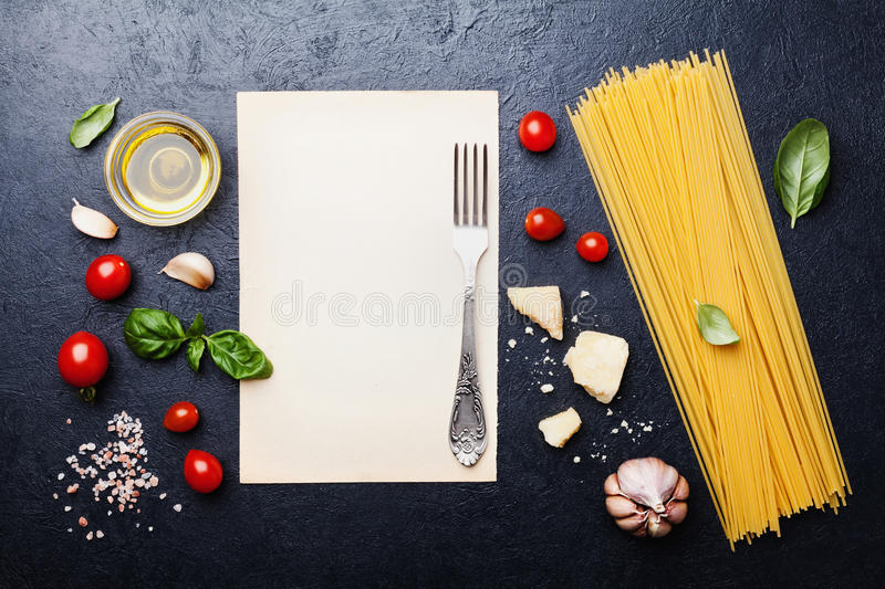 Italian food background with uncooked spaghetti, tomato, basil, cheese, garlic and olive oil for cooking pasta on table from above royalty free stock images