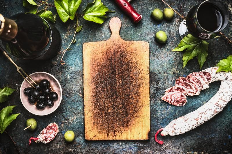 Italian food background with wine, olives and sausage around wooden cutting board royalty free stock images