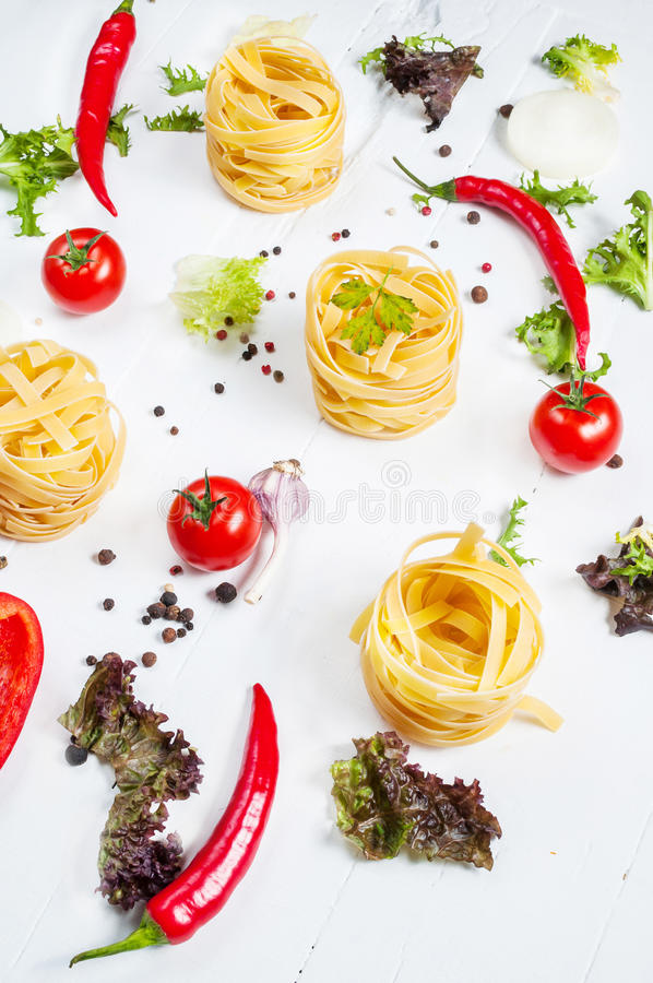 Italian food cooking ingredients. Pasta, tomatoes, peppers on white wooden background stock photography