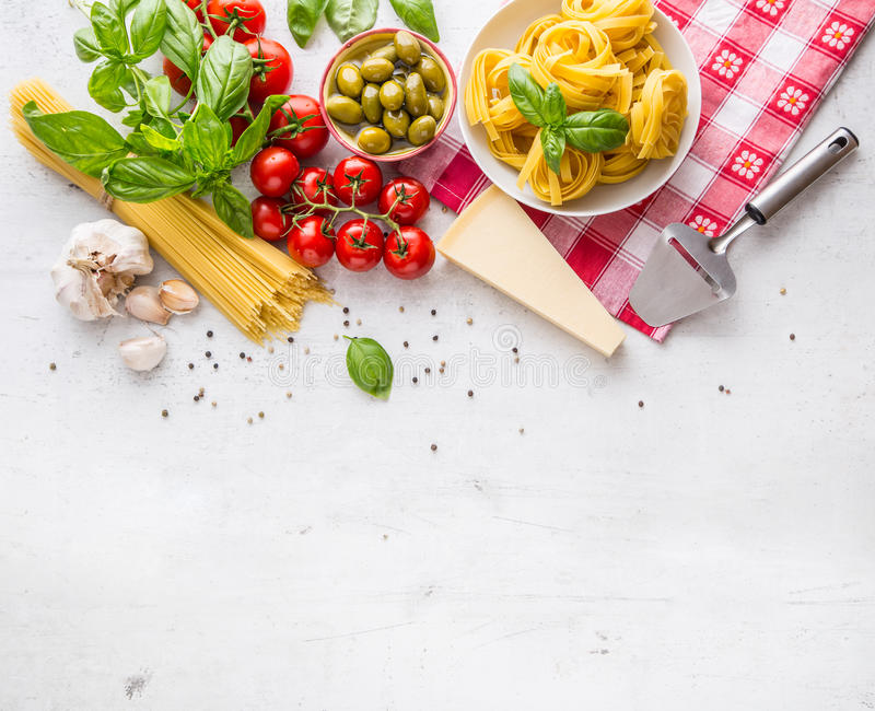 Italian food cuisine and ingredients on white concrete table. Spaghetti Tagliatelle olives olive oil tomatoes parmesan cheese. stock images