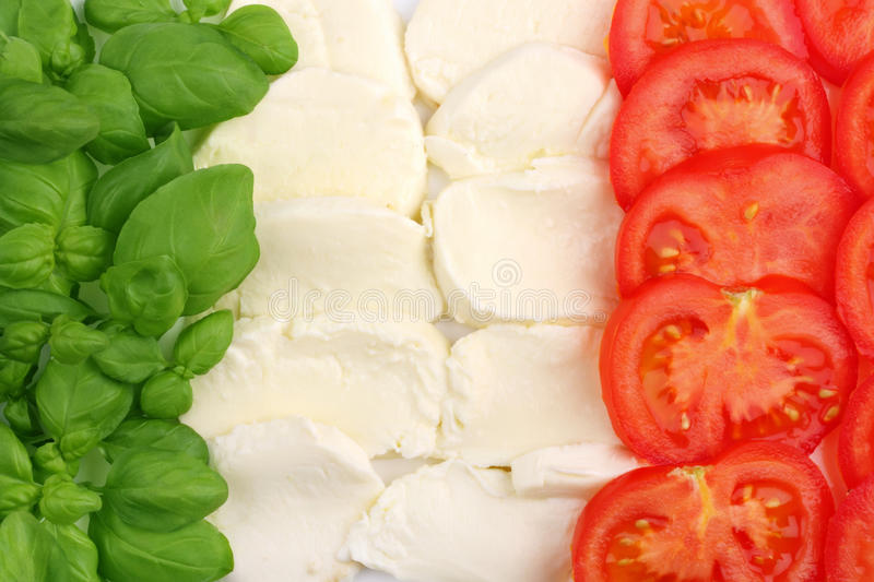 Italian food flag. Basilica leafs, mozzarella cheese and tomatoes forming the italian flag