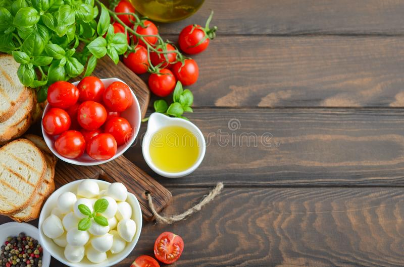 Italian food ingredients – mozzarella, tomatoes, basil and olive oil on rustic wooden table. Italian food ingredients – mozzarella, tomatoes royalty free stock photos