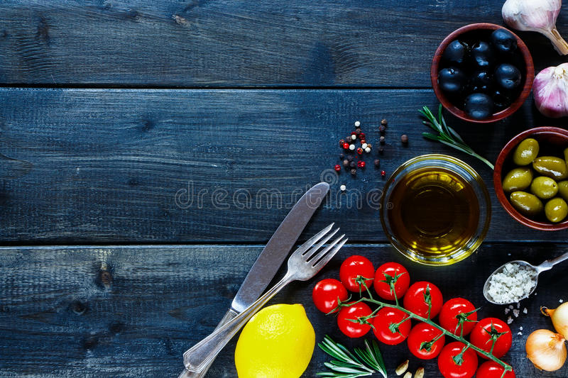 Italian food. Italian ingredients for cooking (tomatoe, garlic, pepper, rosemary, olives, olive oil) on dark wooden background with space for text. Top view royalty free stock photography