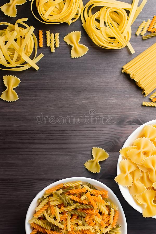 Italian food ingredients frame with various pasta, vegetables, mushrooms, olives. Flat lay on dark wooden background stock photos