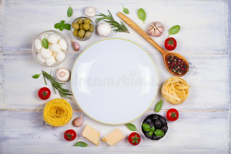 Italian food or ingredients with fresh vegetables, pasta, cheese mozzarella and parmesan, spices. Healthy food background royalty free stock photography