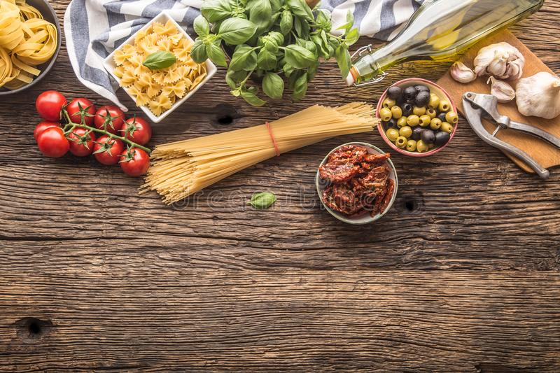 Italian food ingredients pasta olive oil parmesan cheese basil g. Arlic mushrooms tomatoes olives on wooden table stock photo