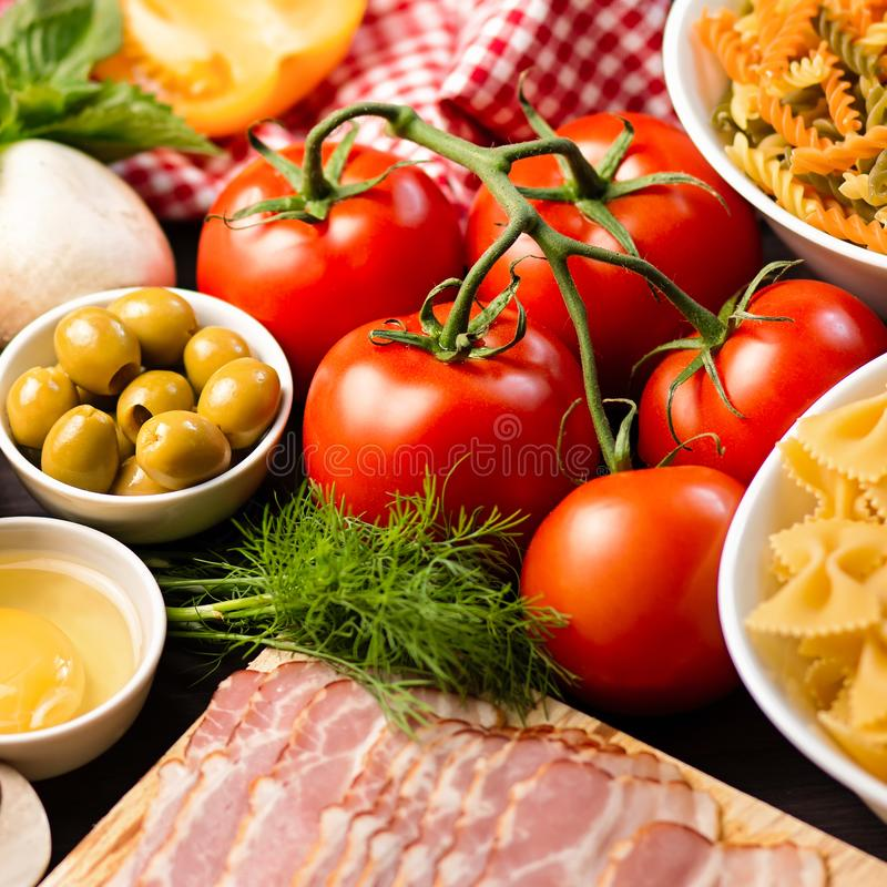 Italian food ingredients - pasta, vegetables, mushrooms, bacon, eggs, olives. Flat lay on dark wooden background royalty free stock photography