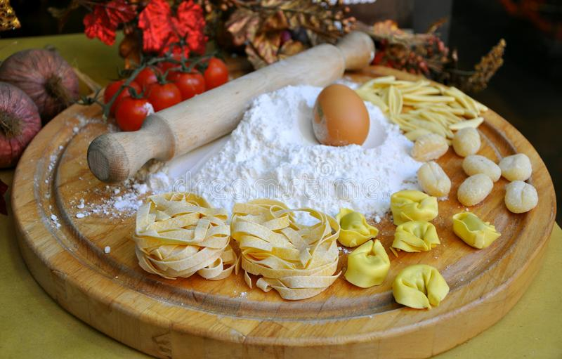 Italian food pasta. Homemade pasta with ingredients on a wooden board: white flour, fresh eggs. Italian restaurant merchendising strategy. Italian food concept stock photography