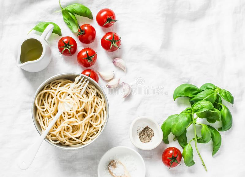 Italian food pasta background with copy space on white background, top view. Basil, whole grain spaghetti, cherry tomatoes, olive royalty free stock photography
