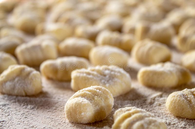 Italian food speciality: hand made potato gnocchi on a wooden board, ready to be cooked. Home made and hand rolled on a fork. Close up, selective focus stock photos