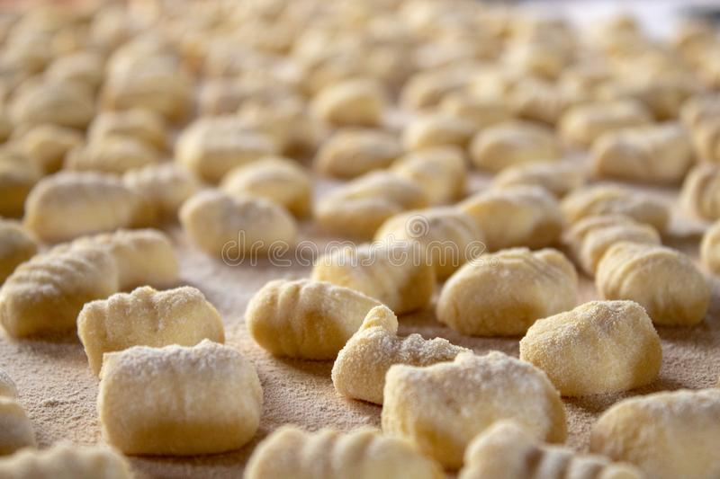 Italian food speciality: hand made potato gnocchi on a wooden board, ready to be cooked. Home made and hand rolled on a fork. Close up, selective focus royalty free stock photos