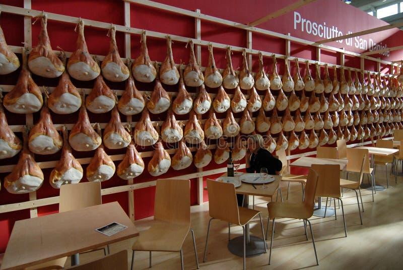 Italian food specialty San Daniele raw hams hung in a food fair stand. Turin Italy circa April 2016 stock photo