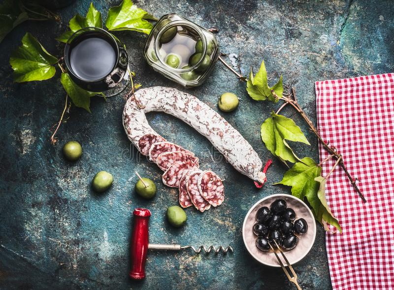 Italian food still life with glass of red wine, olives and sausage on rustic background. Top view royalty free stock images
