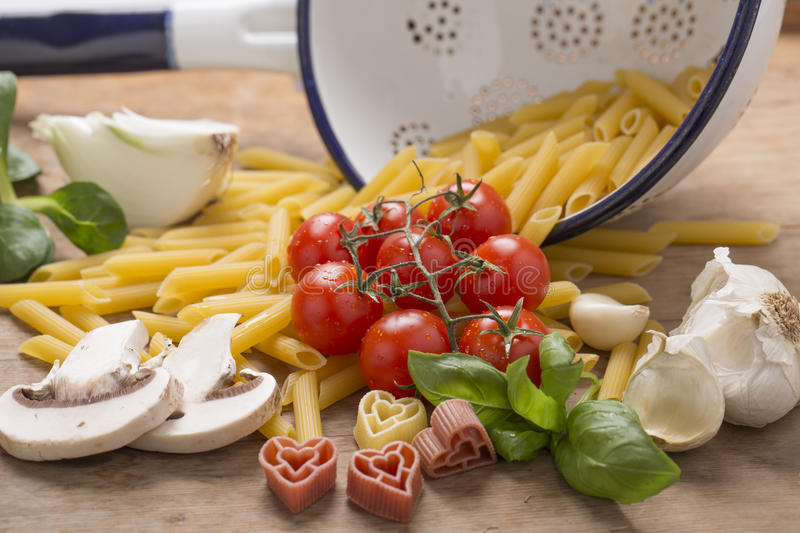 Italian food still life. With pasta, tomatoes, mushroom and basil royalty free stock photo