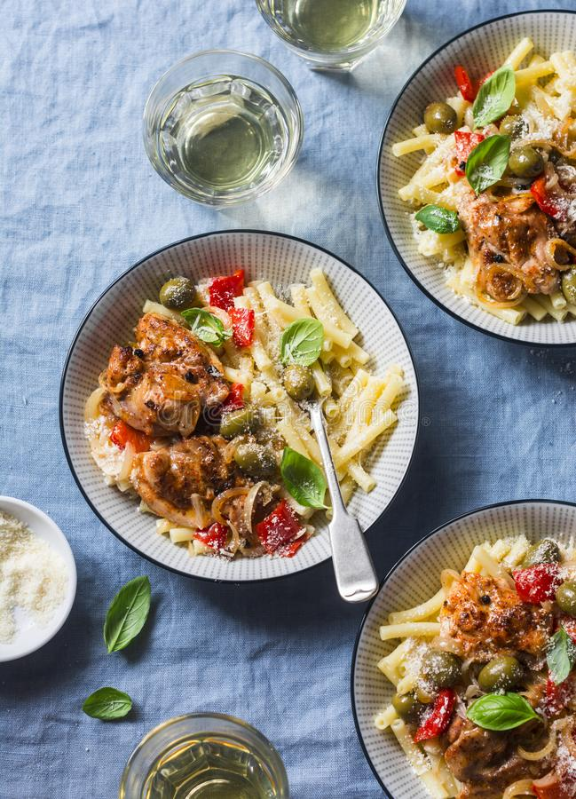 Italian food table. Pasta with slow cooker chicken with olives and sweet peppers, white wine. On a blue background royalty free stock photography