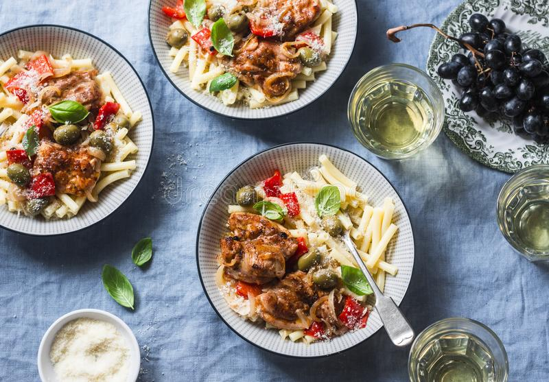 Italian food table. Pasta with slow cooker chicken with olives and sweet peppers, white wine. On a blue background stock photo