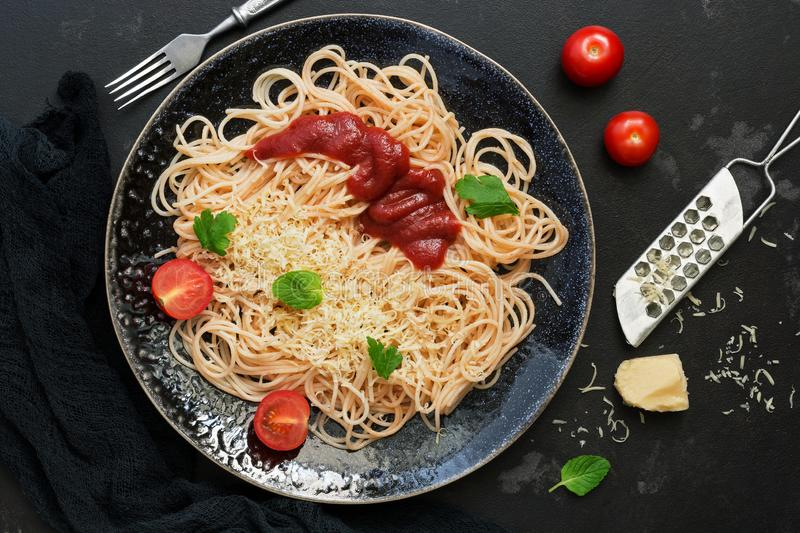 Italian food, traditional pasta spaghetti with tomato sauce, parmesan cheese and greens on a black stone background. View from stock photos
