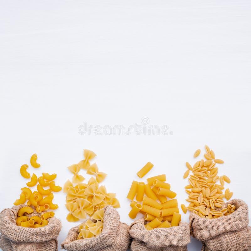 Italian foods concept and menu design . Various kind of Pasta Elbow Macaroni ,Farfalle ,Rigatoni ,gnocco Sardo in hemp sack bags. Setup on white wooden stock image