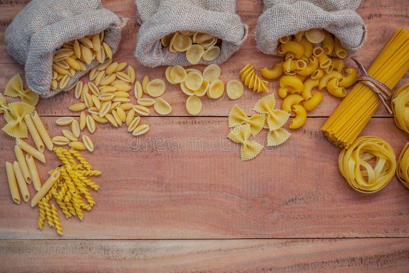 Italian foods concept and menu design . Various kind of Pasta Elbow Macaroni ,Farfalle ,Rigatoni ,gnocco Sardo in hemp sack bags. Set up on brown wooden stock image