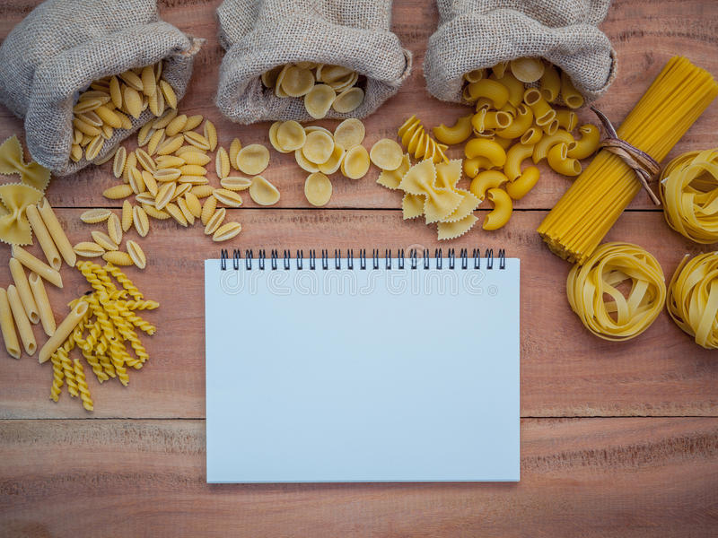 Italian foods concept and menu design . Various kind of Pasta Elbow Macaroni ,Farfalle ,Rigatoni ,gnocco Sardo in hemp sack bags. Set up on brown wooden royalty free stock image