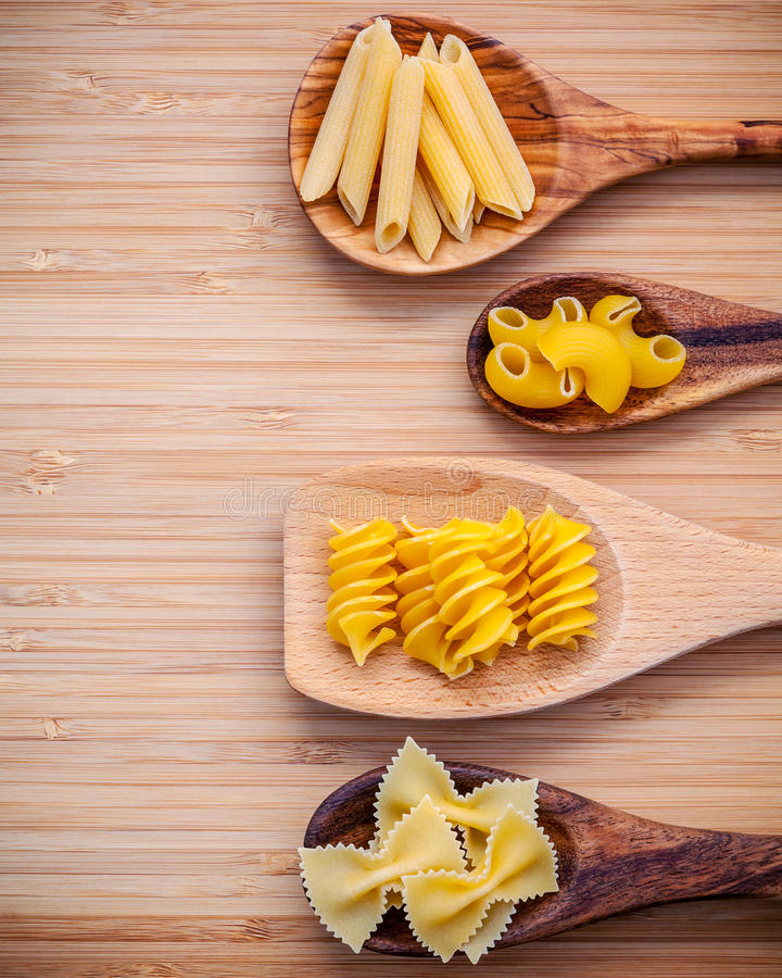 Italian foods concept and menu design . Various kind of Pasta Elbow Macaroni ,Farfalle ,Rigatoni ,Gnocco Sardo in wooden spoons s. Etup on bamboo cutting board royalty free stock images