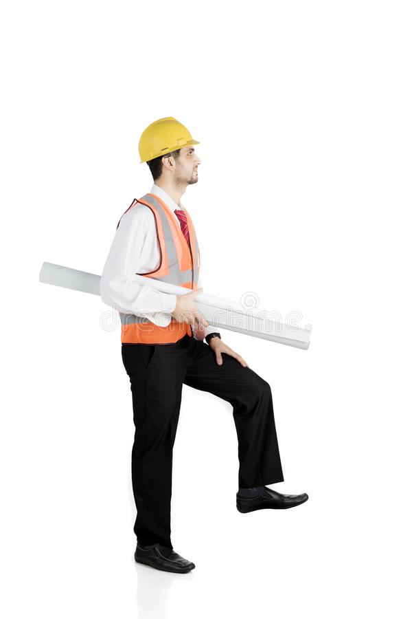 Italian foreman with poses stepping upward. Portrait of Italian foreman carrying blueprints with pose stepping upward, isolated on white background stock images