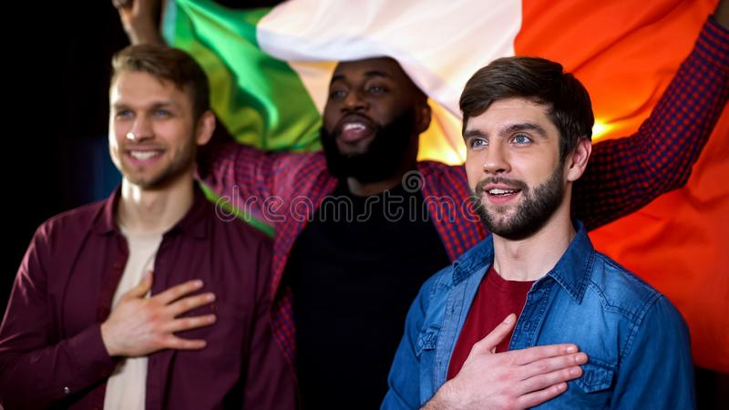 Italian friends with national flag listening to anthem holding hands on hearts. Stock photo royalty free stock photography