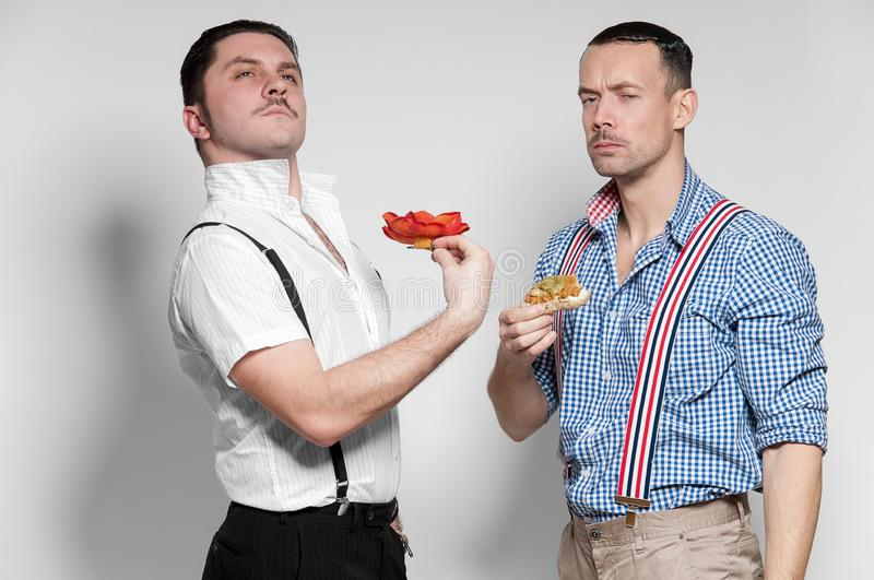 Italian Gangsta and Austrian man posing with funny faces stock photo