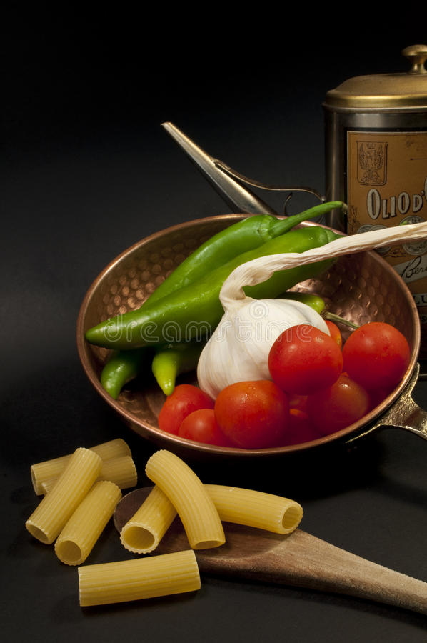 Italian gastronomic composition. Green peppers, garlic, tomatoes, pasta and Italian oil stock image