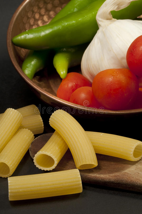 Italian gastronomic composition. Green peppers, garlic, tomatoes, pasta and Italian oil royalty free stock photography