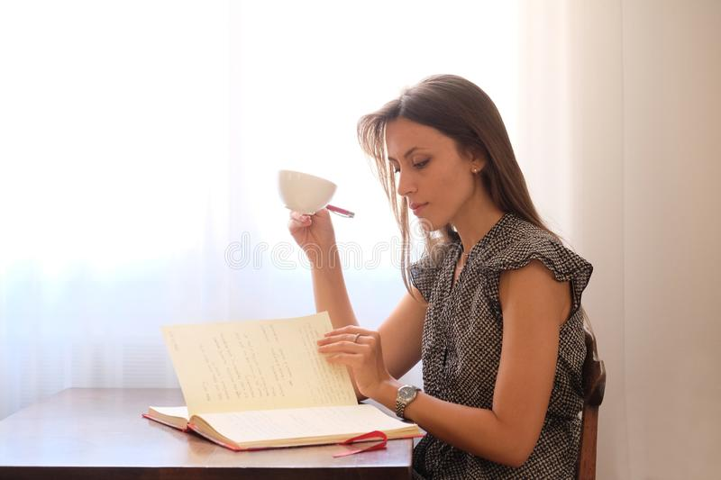 Girl sitting on a chair reads a book and drinks coffee royalty free stock image