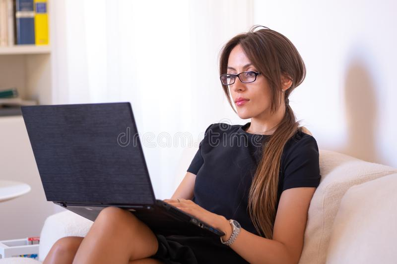 Girl sitting on a sofa writes on her computer stock photography