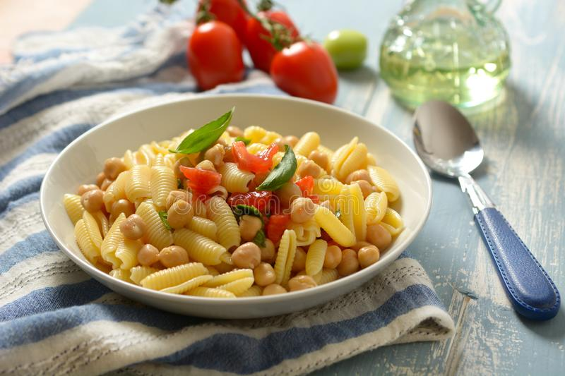 Italian gnocchi pasta with tomatoes, basil and chickpeas - close royalty free stock images