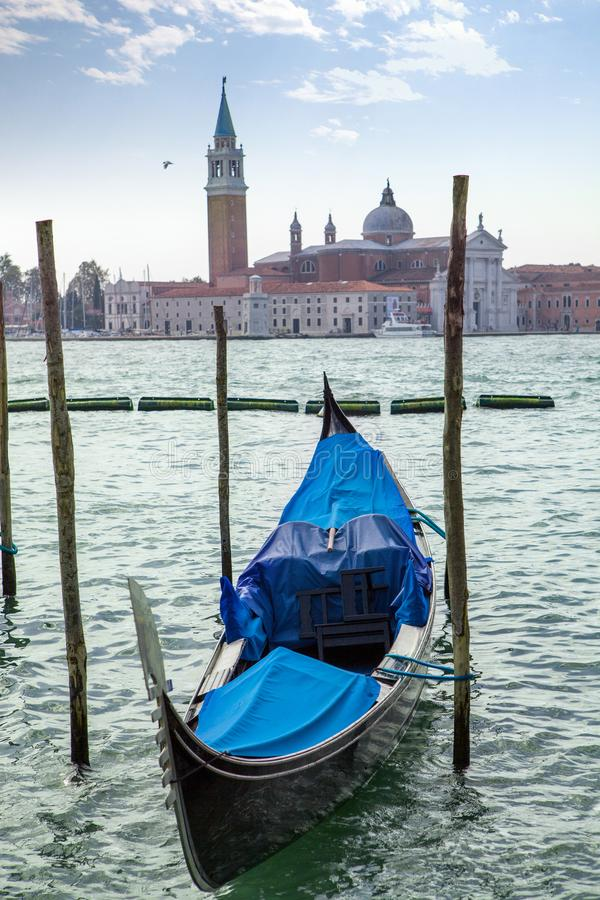 Italian gondola parking on the water in Venice, Italia. Travel boat italian gondola parking on the water on the background of San Giorgio Maggiore in Venice royalty free stock image