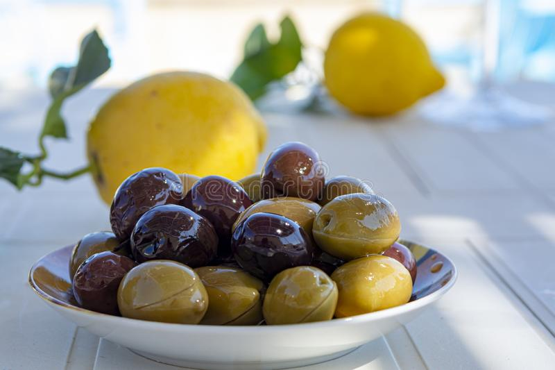 Italian green and black olives in olive oil close up. Served outdoor on white table stock image