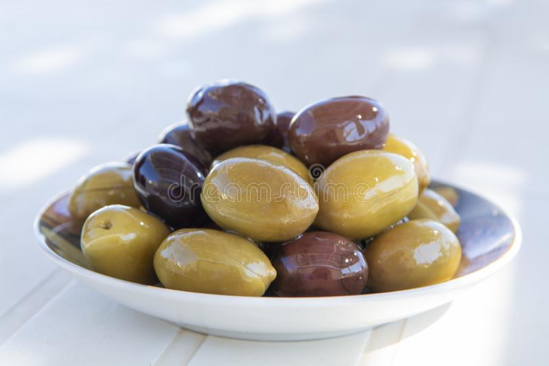 Italian green and black olives in olive oil close up. Served outdoor on white table royalty free stock photography
