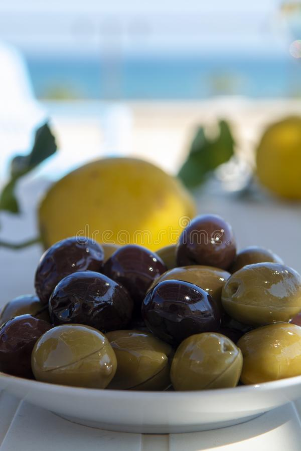 Italian green and black olives in olive oil close up. Served outdoor on white table royalty free stock photos