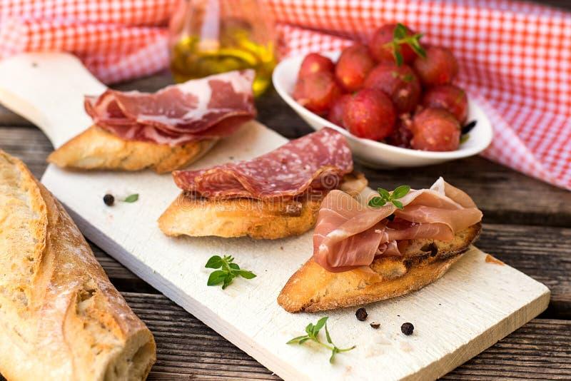 Italian ham dry cured prosciutto on bread toast. Bruschetta royalty free stock image