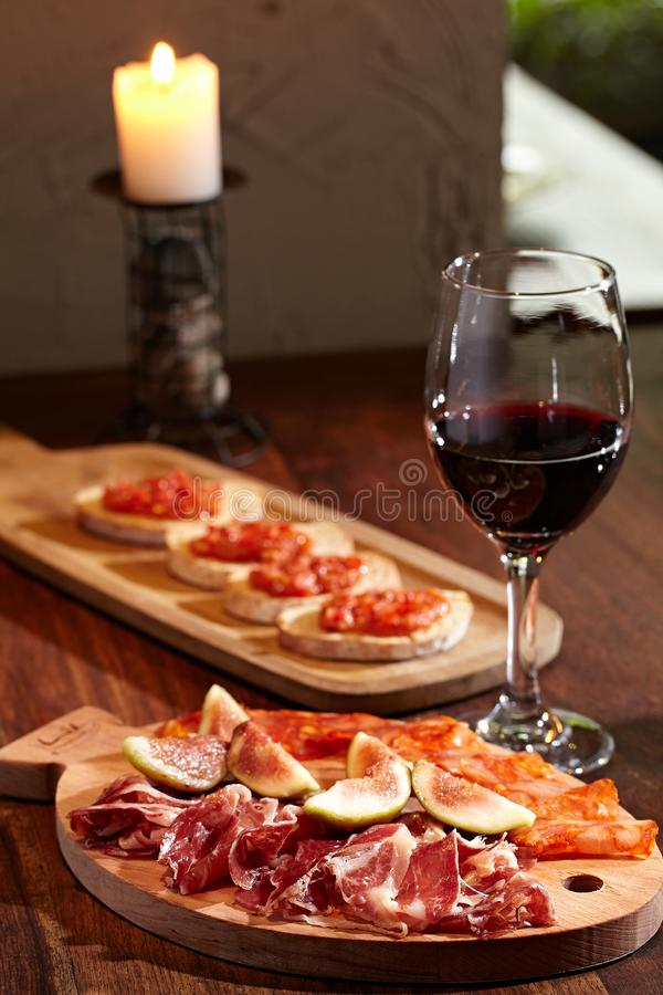 Italian ham on a wooden tray and red wine in a goblet with a candlestick in the background. royalty free stock image